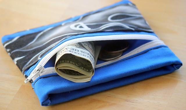 wallet zipper open with dollar bill sticking out
