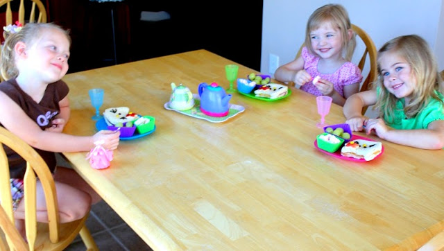 3 little girls eating sandwiches at kitchen table