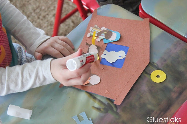 child gluing nativity scene characters onto manger with glue stick