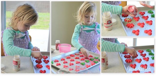 little girl adding sprinkles to cookies