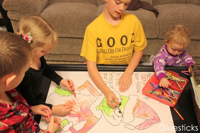 children sitting at table coloring grinch poster