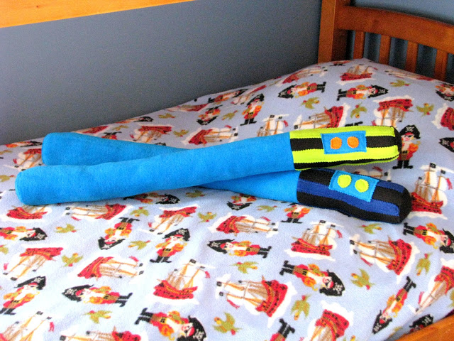 2 light saber pillows on twin sized bed