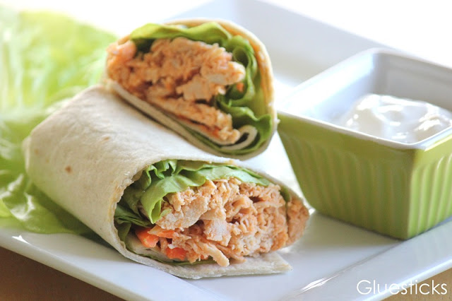 buffalo chicken wrap on white plate with small bow of ranch
