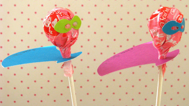 two lollipops with paper capes and masks