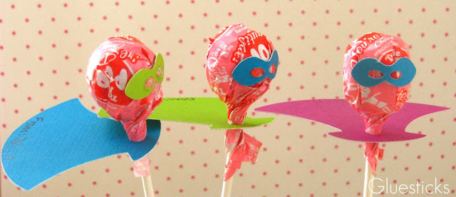 3 lollipops with paper capes and masks