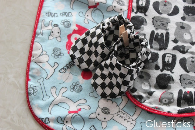 fabric baby shoes on top of receiving blanket