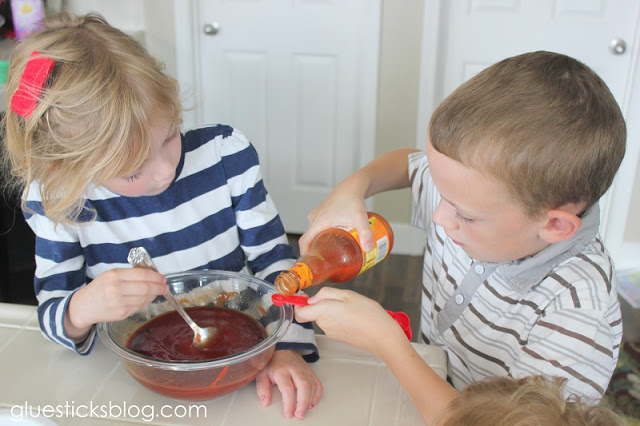 child pouring in hot sauce into teaspoon
