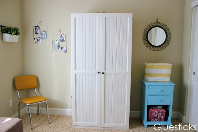 craft room with chair and large wooden craft storage hutch and sewing machine table