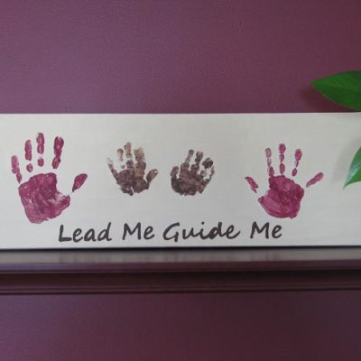 4 child handprints painted on canvas