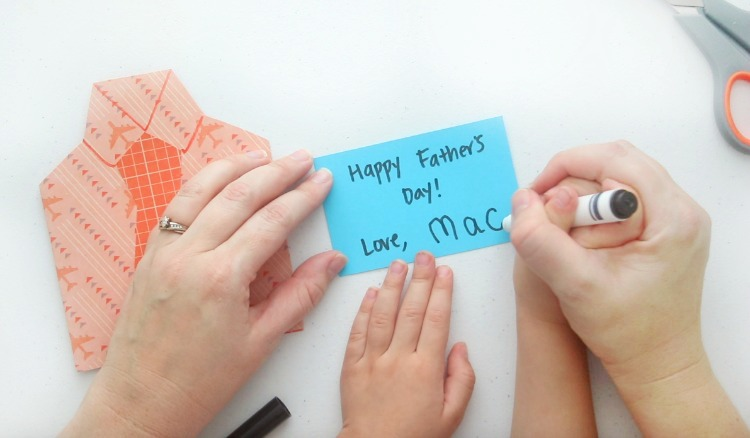 mom and child writing message inside card