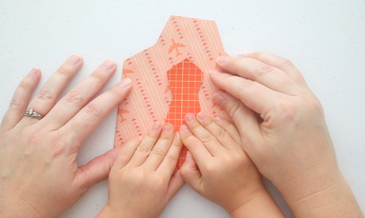 child hands gluing paper tie onto card