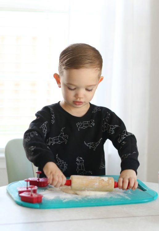 toddler rolling out salt dough with rolling pin