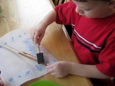 child painting wooden dowel with brown paint