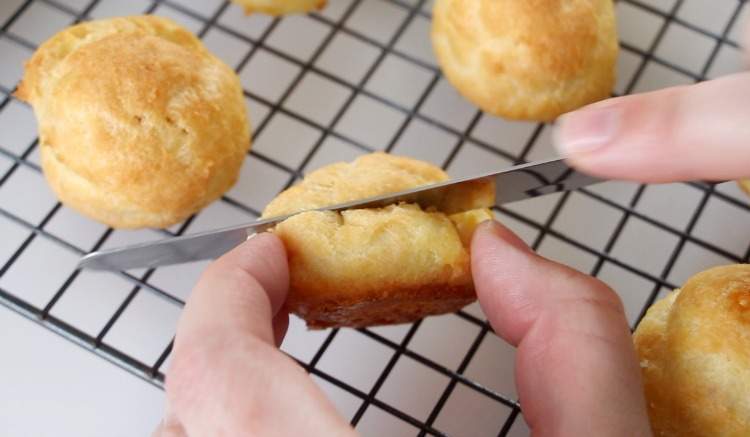 slicing top off of cream puff with a sharp knife