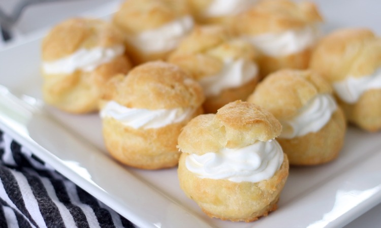 finished cream puffs on white platter