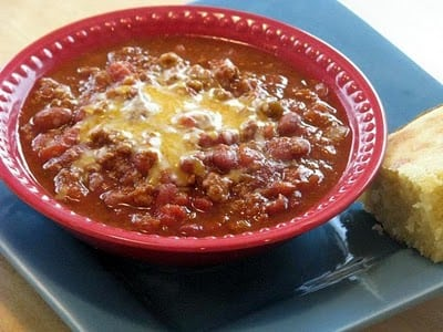 turkey chili with cheese in red bowl