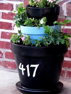 tiered terracotta planter with house numbers painted on front