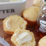 cornbread muffin sliced with butter and bottle of honey next to it