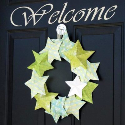 paper star wreath hanging on black door