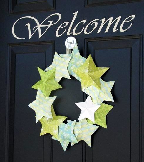 paper star wreath hanging on black door