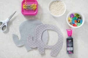 two felt elephant cut outs with pins, rice, small trinkets and fabric paint