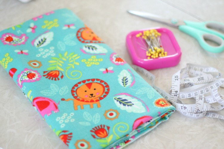 folded fabric with pins, scissors and a measuring tape