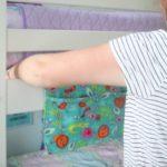 woman sliding book caddy under mattress on bunkbed