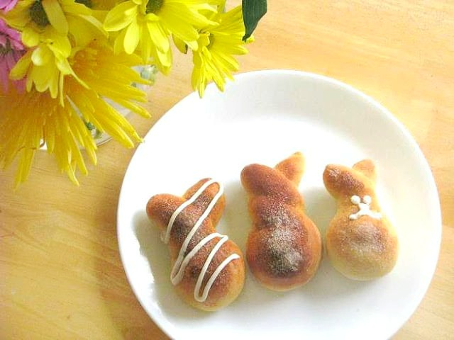 cinnamon bunny rolls on white plate next to vase of yellow flowers