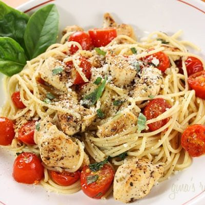 white plate with spaghetti tomatoes chicken and basil