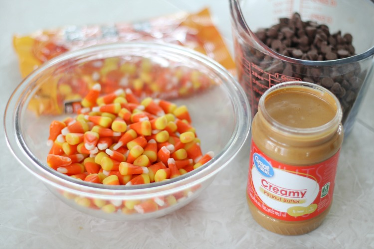 bowl of candy corn, container of peanut butter and bowl of chocolate chips