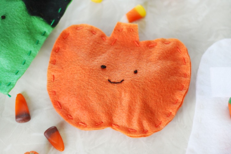 orange felt pumpkin pouch with face stitched on
