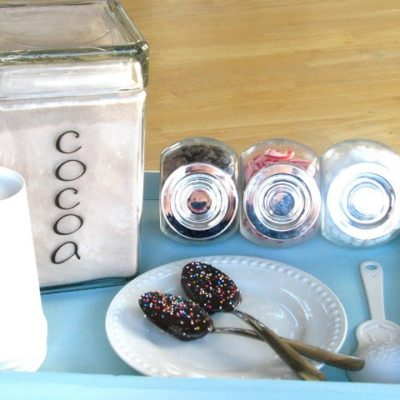 blue wooden tray with hot cocoa mix and chocolate spoons
