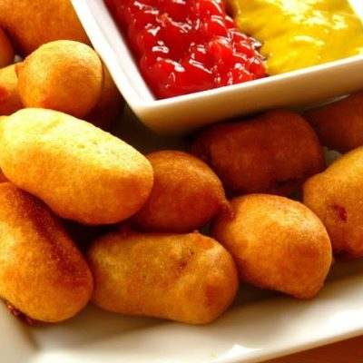 mini corn dogs on plate with bowl of condiments