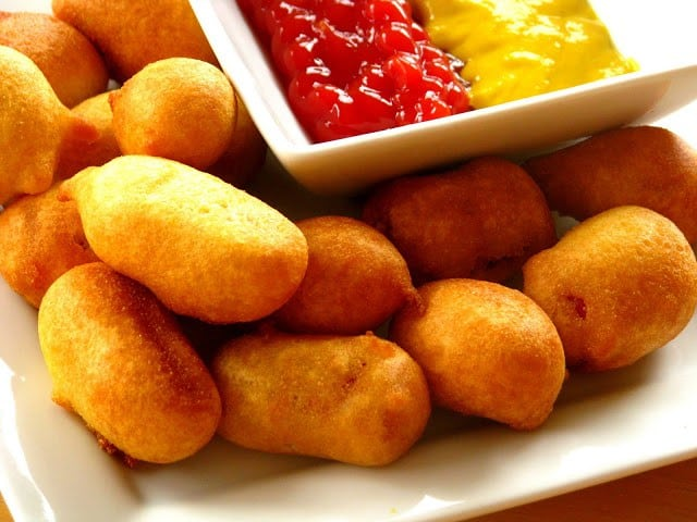 mini corn dogs on plate with bowl of ketchup and mustard