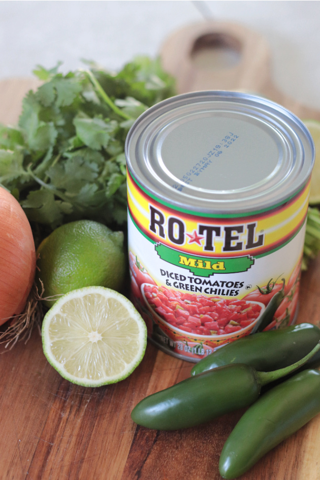 can of rotel, jalapeños, limes, onion and cilantro on cutting board