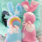 young girl holding two fleece bunnies