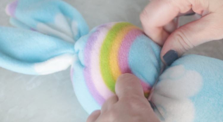 hands tying a piece of yarn around fleece bunny