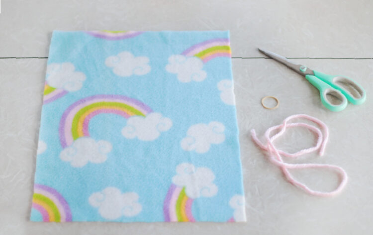 rectangle of fleece, yarn, rubber band and scissors