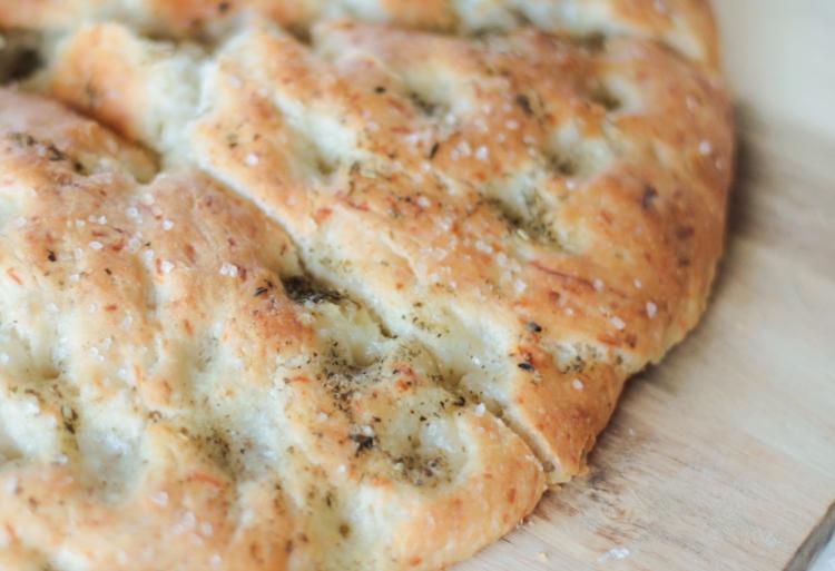 sliced focaccia bread on cutting board