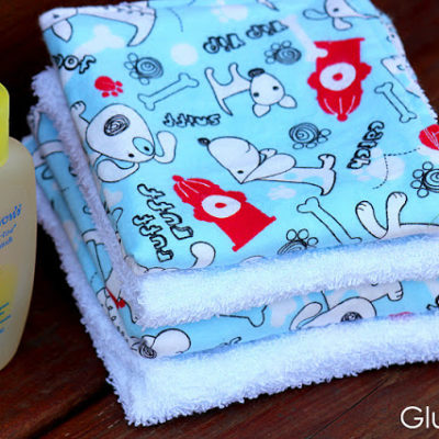 3 baby wash cloths stacked with bottle of baby shampoo