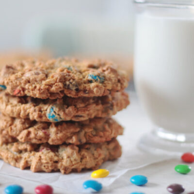 4 monster cookies stacked next to a glass of milk