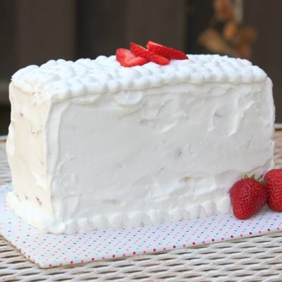 uncut pound cake frosted with whipped cream