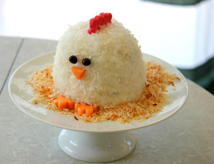 chicken cake covered in coconut on cake platter