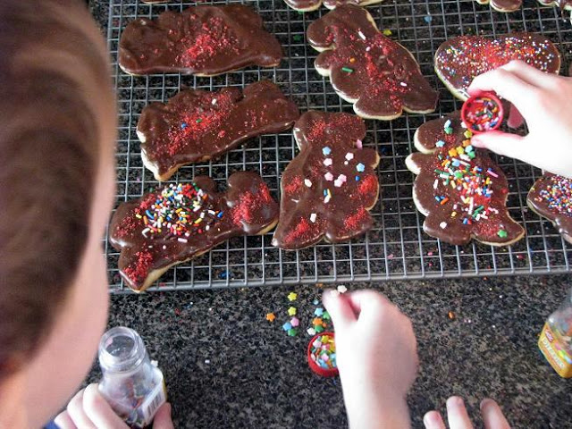 little boys adding sprinkles to chocolate sugar cookies