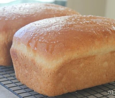 two loaves of amish white bread on cooling rack