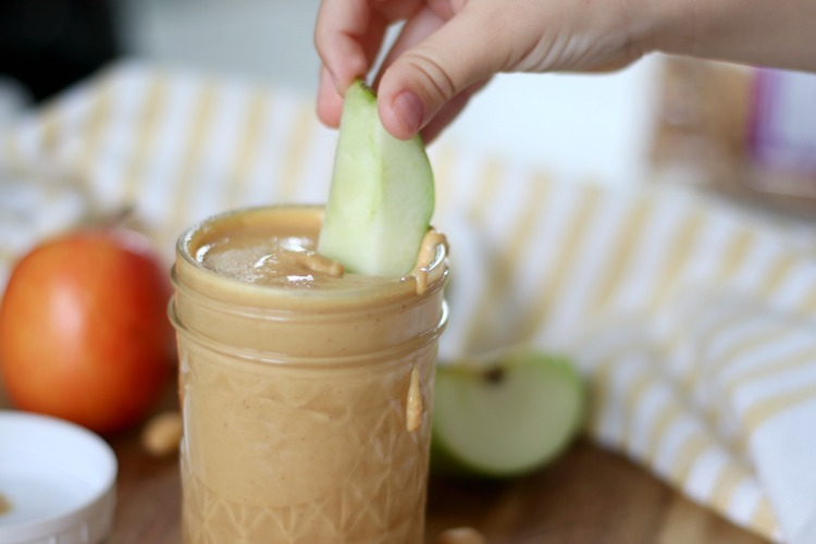 apple slice dipped in jar of peanut butter