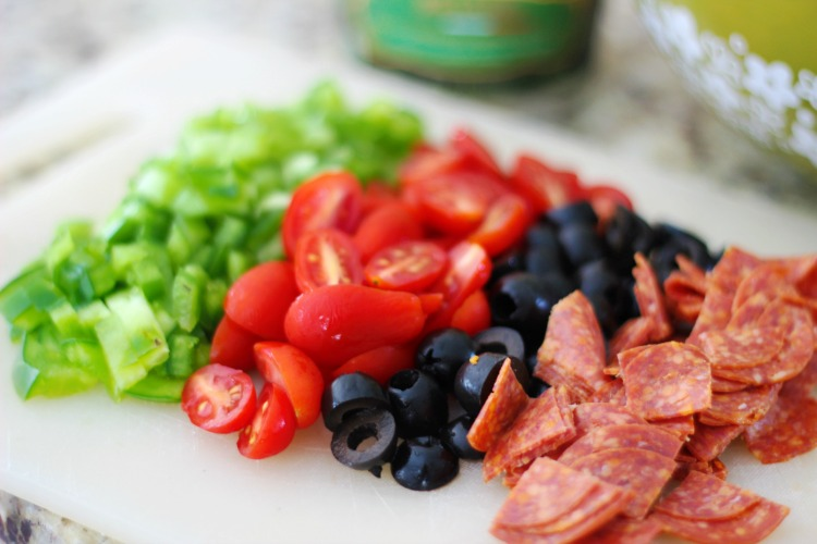 pasta salad ingredients diced on cutting board