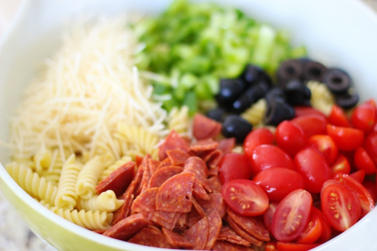 cooked pasta, pepperoni, diced tomatoes, olives, peppers and cheese in a large bowl