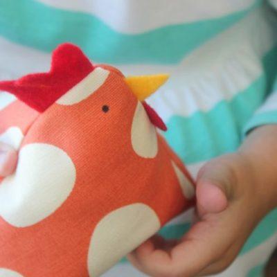 child holding chicken bean bag