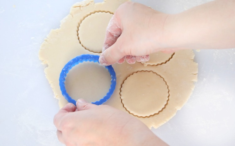 rolled sugar cookie dough being cut into shapes